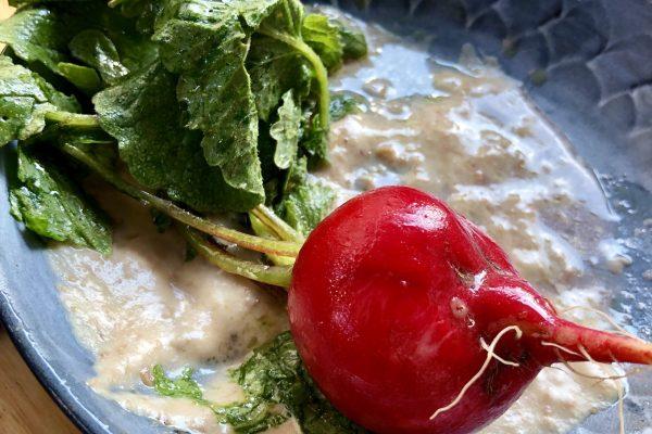 Dressed radish and radish greens on hummus, at Manfreds